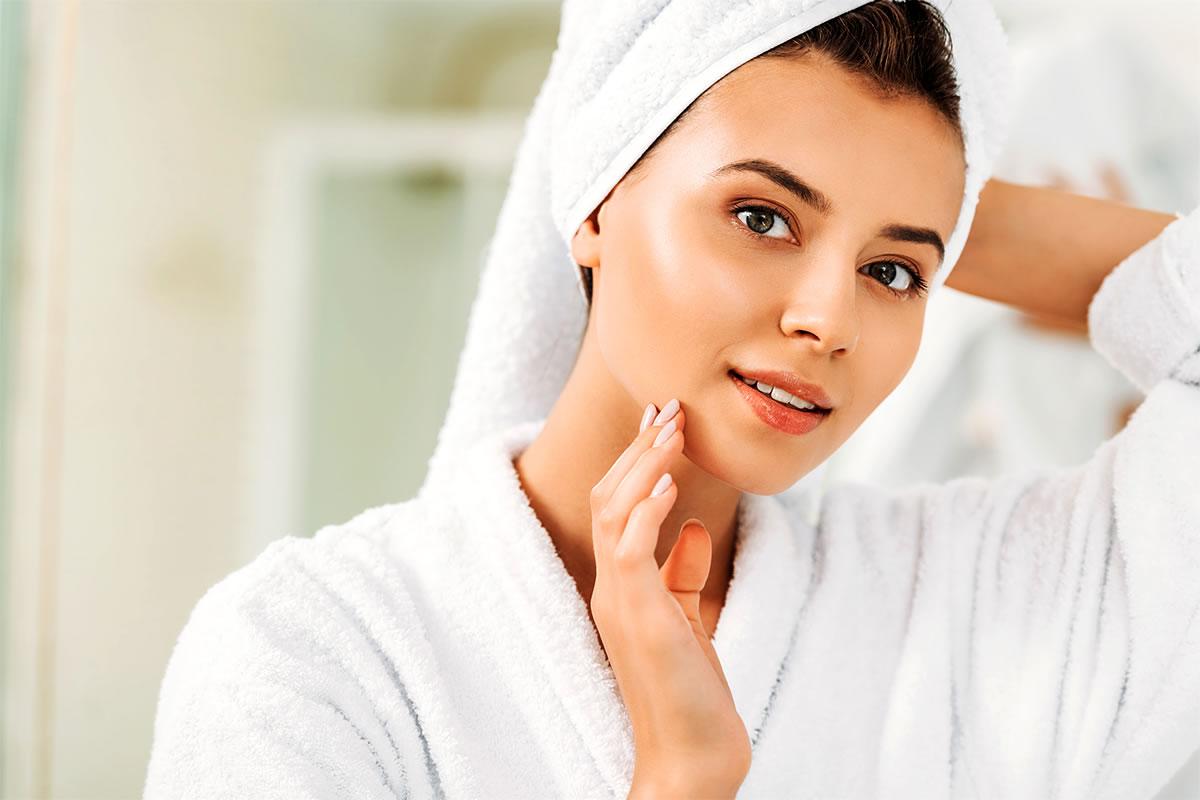 kobieta z piękną cerą w ręczniku na głowie przegląda się w lustrze
