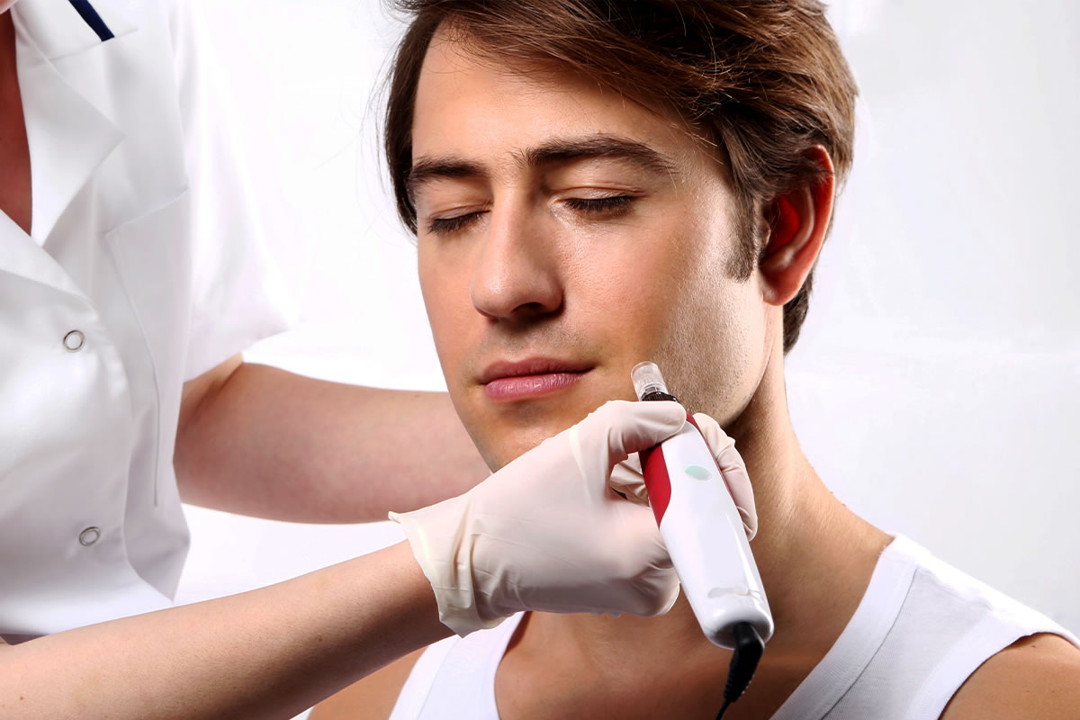 młody mężczyzna podczas mezoterapii mikroigłowej twarzy